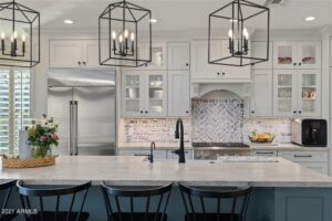 Modern kitchen featuring large island with marble countertop and four black bar stools.