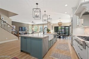 Modern kitchen with wood flooring, white appliances, and a cooking island.