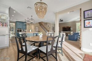 Luxurious kitchen and dining area with wood flooring, dark brown chairs, and a large island